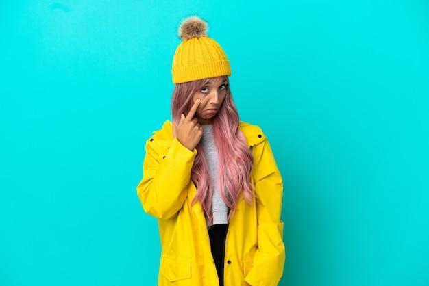 Junge frau mit rosa haaren, die einen regendichten mantel trägt, der auf blauem hintergrund isoliert ist und etwas zeigt