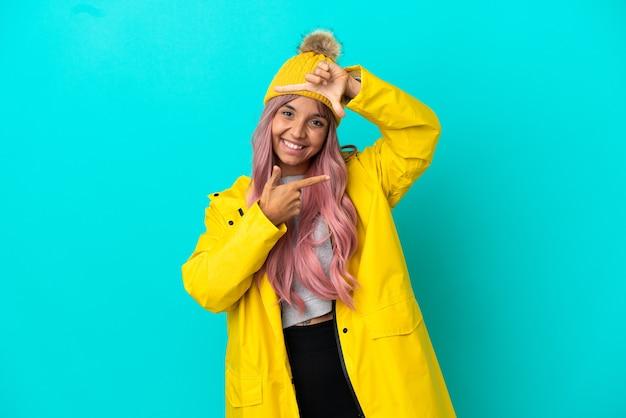 Junge frau mit rosa haaren, die einen regendichten mantel trägt, isoliert auf blauem hintergrund, der das gesicht fokussiert. rahmensymbol