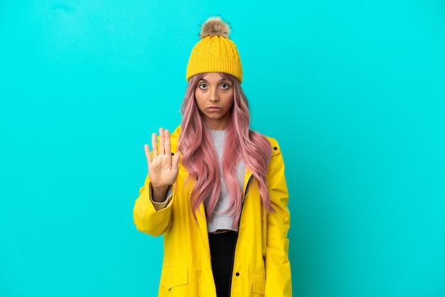Junge frau mit rosa haaren, die einen regendichten mantel trägt, isoliert auf blauem hintergrund, der eine stopp-geste macht