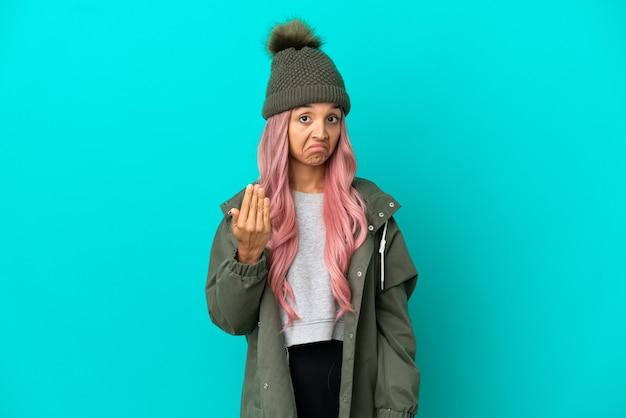 Junge frau mit rosa haaren, die einen regendichten mantel trägt, isoliert auf blauem hintergrund, der einlädt, mit der hand zu kommen. schön, dass du gekommen bist