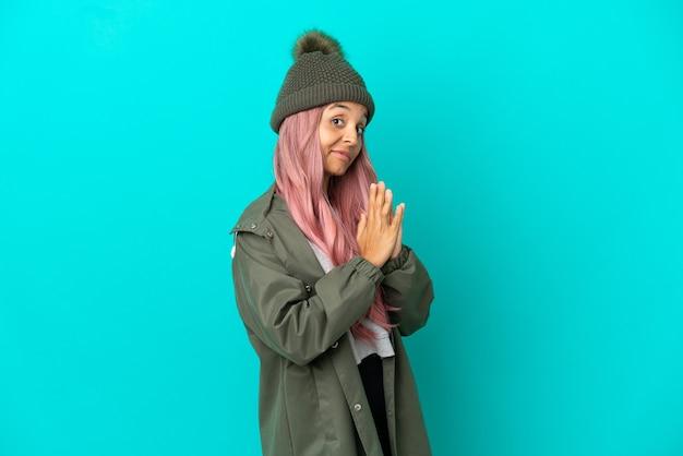 Junge frau mit rosa haaren, die einen regendichten mantel trägt, isoliert auf blauem hintergrund, der etwas inszeniert