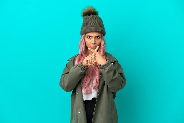 Junge frau mit rosa haaren, die einen regendichten mantel trägt, isoliert auf blauem hintergrund, der mit der hand eine stoppgeste macht, um eine handlung zu stoppen