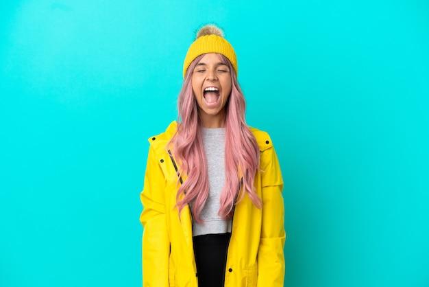 Junge frau mit rosa haaren, die einen regendichten mantel trägt, isoliert auf blauem hintergrund, der mit weit geöffnetem mund nach vorne schreit