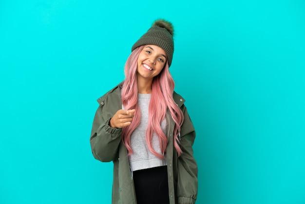 Junge frau mit rosa haaren, die einen regendichten mantel trägt, isoliert auf blauem hintergrund, der nach vorne mit glücklichem ausdruck zeigt