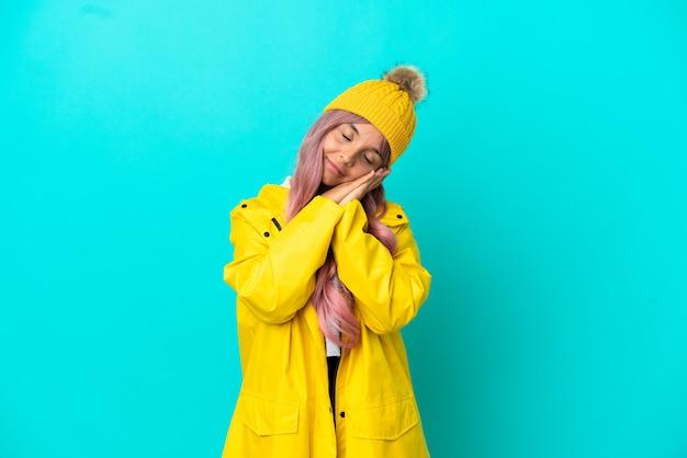 Junge frau mit rosa haaren, die einen regendichten mantel trägt, isoliert auf blauem hintergrund, der schlafgeste in entzückender ausdrucksweise macht