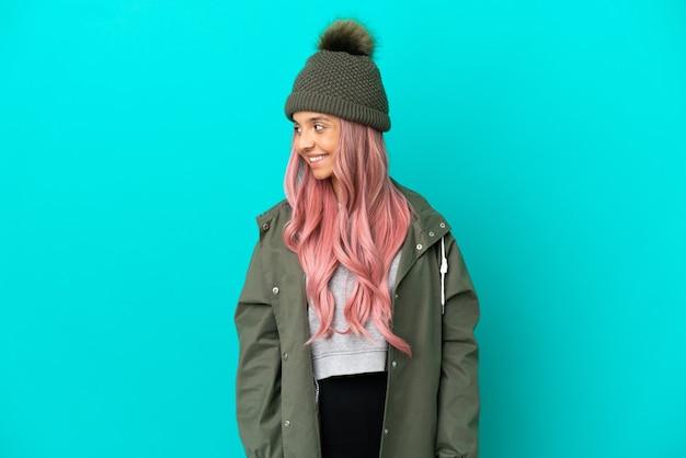 Junge frau mit rosa haaren, die einen regendichten mantel trägt, isoliert auf blauem hintergrund, der zur seite schaut und lächelt