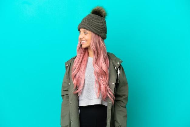 Junge frau mit rosa haaren, die einen regendichten mantel trägt, isoliert auf blauem hintergrund, der zur seite schaut