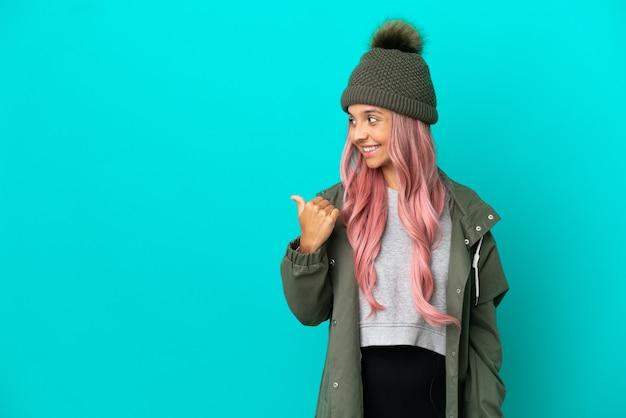 Junge frau mit rosa haaren, die einen regendichten mantel trägt, isoliert auf blauem hintergrund, der zur seite zeigt, um ein produkt zu präsentieren