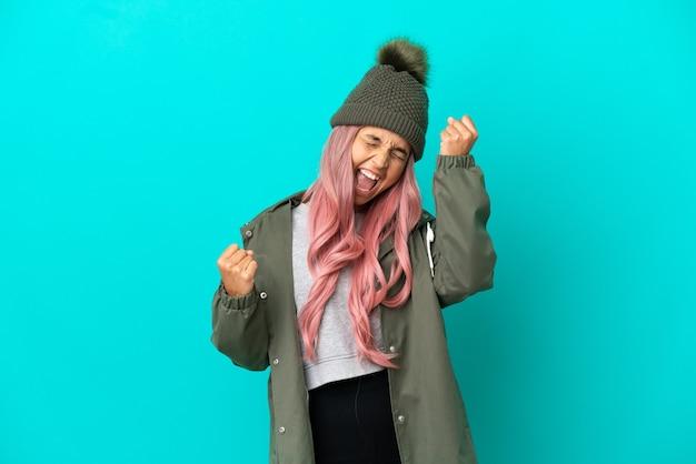 Junge frau mit rosa haaren, die einen regendichten mantel trägt, isoliert auf blauem hintergrund, feiert einen sieg