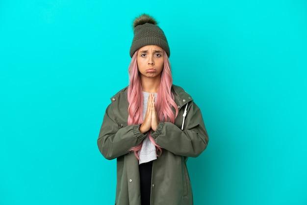 Junge frau mit rosa haaren, die einen regendichten mantel trägt, isoliert auf blauem hintergrund, hält die handfläche zusammen. person fragt nach etwas