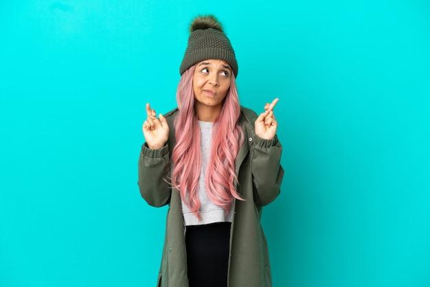 Junge frau mit rosa haaren, die einen regendichten mantel trägt, isoliert auf blauem hintergrund mit gekreuzten fingern und das beste wünscht
