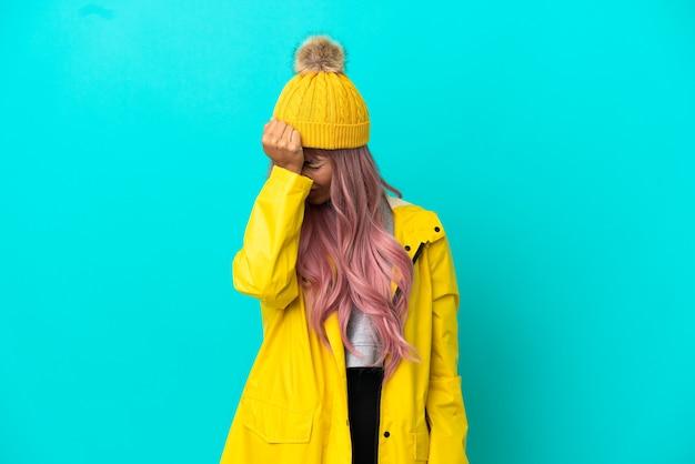 Junge frau mit rosa haaren, die einen regendichten mantel trägt, isoliert auf blauem hintergrund mit kopfschmerzen