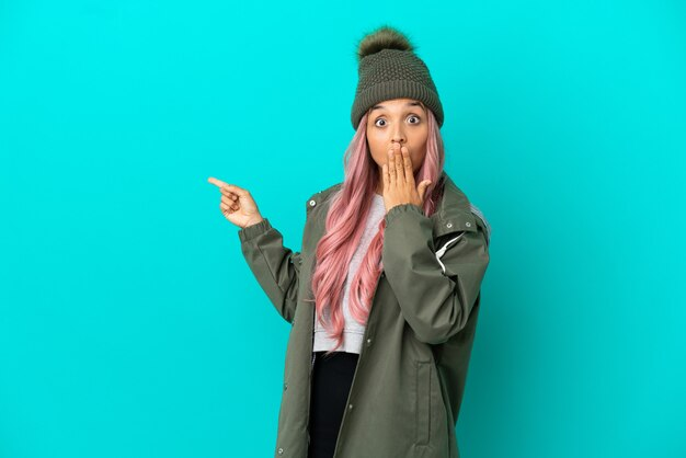 Junge frau mit rosa haaren, die einen regendichten mantel trägt, isoliert auf blauem hintergrund mit überraschungsausdruck, während sie auf die seite zeigt