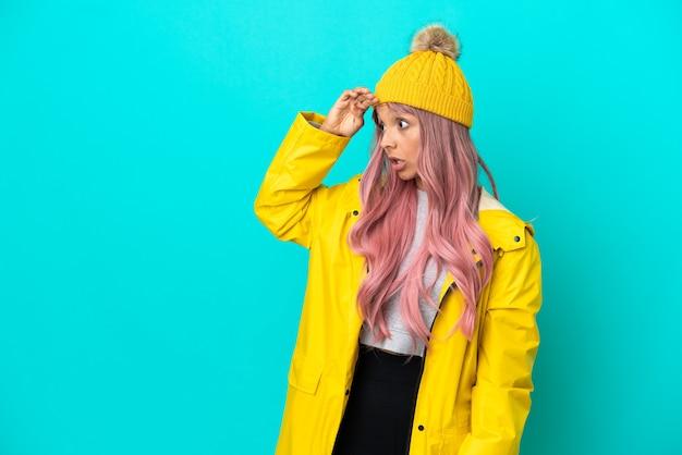 Junge frau mit rosa haaren, die einen regendichten mantel trägt, isoliert auf blauem hintergrund mit überraschungsausdruck, während sie zur seite schaut