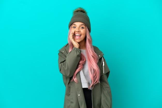 Junge frau mit rosa haaren, die einen regendichten mantel trägt, isoliert auf blauem hintergrund, schreiend mit weit geöffnetem mund