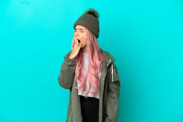 Junge frau mit rosa haaren, die einen regenfesten mantel trägt, isoliert auf blauem hintergrund, gähnt und bedeckt den weit geöffneten mund mit der hand