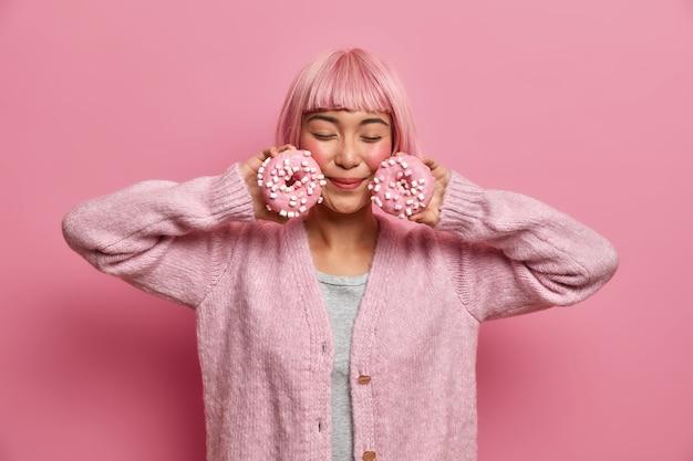 Junge frau mit rosa haaren genießt den geschmack köstlicher donuts, posiert mit geschlossenen augen, hält mit süßigkeiten bestreute donuts in der nähe des gesichts, trägt einen warmen pullover,