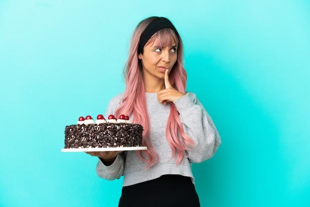 Junge frau mit rosa haaren hält geburtstagskuchen isoliert auf blauem hintergrund und hat zweifel beim nachschlagen