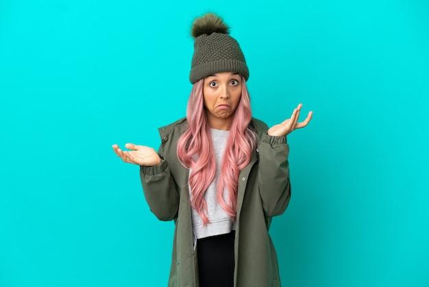 Junge frau mit rosa haaren trägt einen regendichten mantel auf blauem hintergrund isoliert und macht zweifel