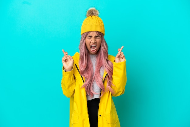 Junge frau mit rosa haaren trägt einen regendichten mantel auf blauem hintergrund mit gekreuzten fingern
