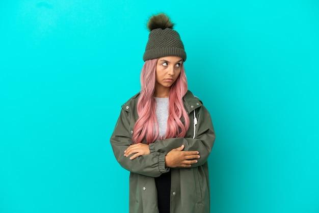 Junge frau mit rosa haaren trägt einen regenfesten mantel auf blauem hintergrund isoliert und hält die arme verschränkt