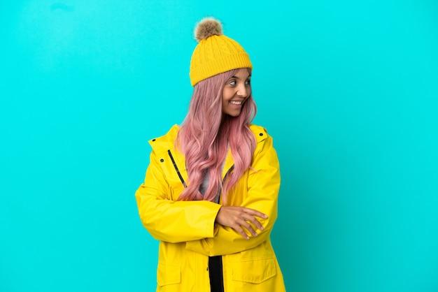 Junge frau mit rosa haaren trägt einen regenfesten mantel auf blauem hintergrund mit verschränkten armen und glücklich