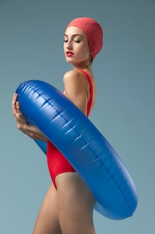 Junge frau mit rotem badeanzug und einem schwimmring