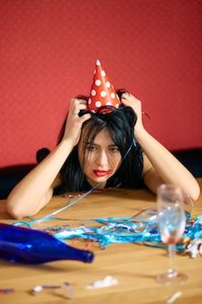 Junge frau mit rotem geriebenem lippenstift und mütze, die nach der geburtstagsfeier müde am tisch in einem unordentlichen zimmer sitzt?