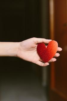 Junge frau mit rotem glitzerndem herzförmigem karton auf der hand. mädchen, das ein pappherz für st hält. valentinstag. liebes- und valentinskonzept.