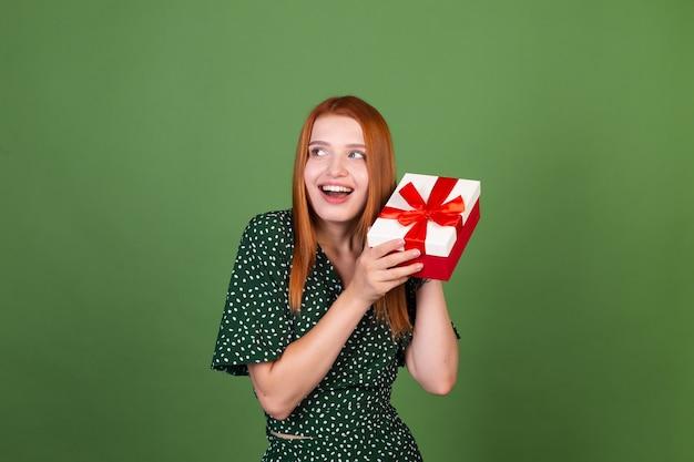 Junge frau mit rotem haar auf grüner wand mit geschenkbox glücklich aufgeregt überrascht überrascht