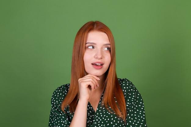 Junge frau mit rotem haar auf grüner wand nachdenkliches fragen