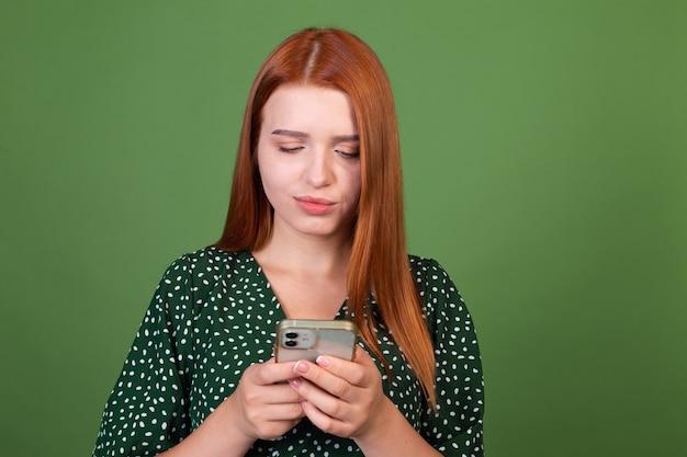 Junge frau mit roten haaren auf grüner wand mit handy-sms, die mit einem lächeln im gesicht plaudert, glücklich positiv