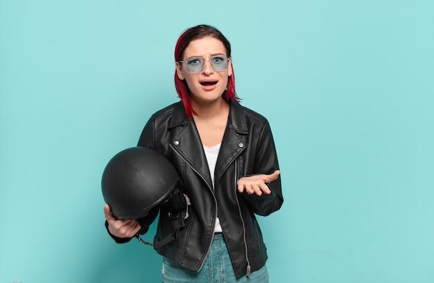 Junge frau mit roten haaren, die wütend, genervt und frustriert aussieht und wtf schreit oder was mit dir los ist. motorradfahrer-konzept
