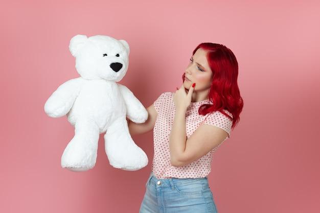Junge frau mit roten haaren hält einen großen weißen teddybär und reibt sich mit der hand das kinn
