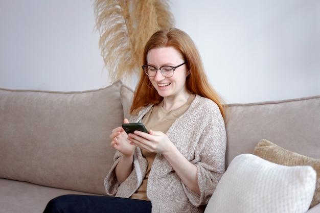 Junge frau mit roten haaren in gläsern, die zu hause auf der couch sitzen und im internet surfen