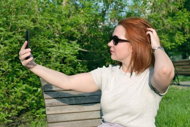 Junge frau mit roten haaren in sonnenbrille glättet ihr haar, um ein foto von sich selbst am telefon zu machen. frau macht ein selfie auf einem smartphone in einem stadtpark.