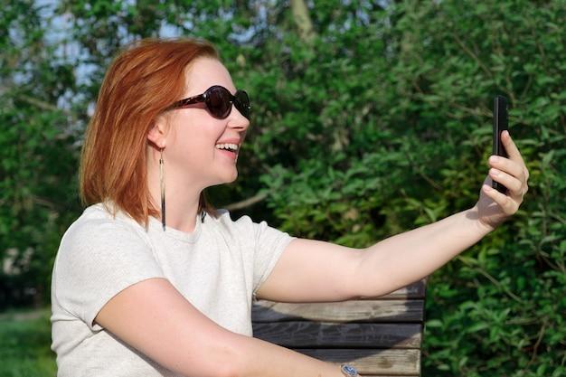 Junge frau mit roten haaren in sonnenbrille lächelt mit ausgestreckter hand auf den bildschirm seines smartphones, um ein foto von sich selbst am telefon zu machen. frau macht ein selfie auf einem smartphone in einem stadtpark.