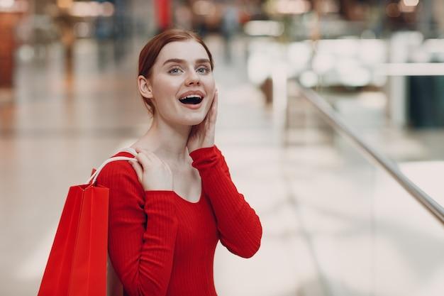Junge frau mit roten papiertüten im einkaufszentrum. schwarzer freitag und valentinstag konzept