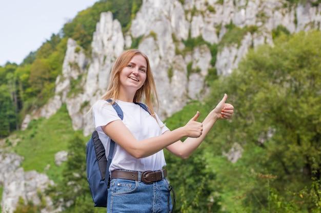 Junge frau mit rucksack, der daumen aufgibt. trekking- und tourismuskonzept.