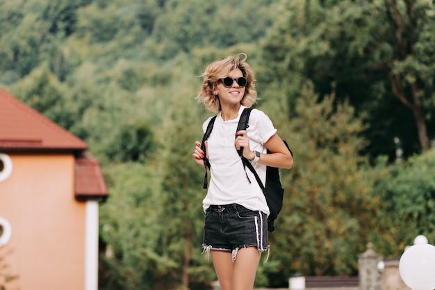 Junge frau mit rucksack, der in den bergen mit erhobenen händen reist und talblick, reise, abenteuer, straße, reisender beobachtet