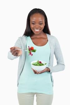 Junge frau mit salat auf ihrer gabel