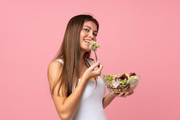 Junge frau mit salat über getrennter rosafarbener wand