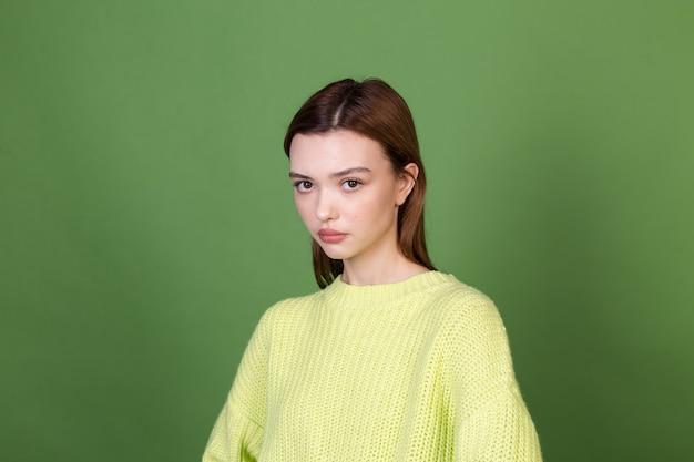 Junge frau mit sauberer perfekter natürlicher haut und make-up braune große lippen auf grüner wand unglücklich traurig enttäuscht