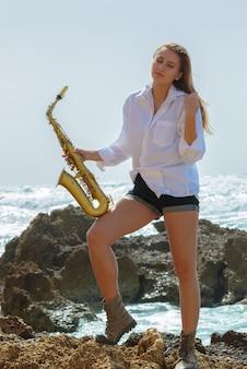 Junge frau mit saxophon bleiben am meeresstrand