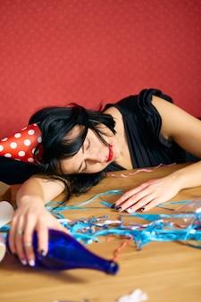 Junge frau mit schlafen am tisch in einem unordentlichen zimmer nach der geburtstagsfeier
