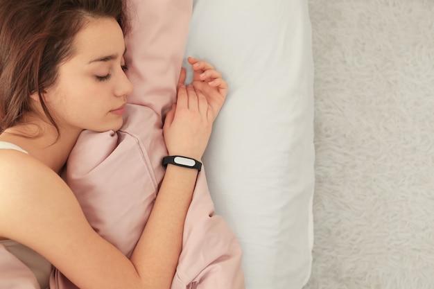 Junge frau mit schlaftracker, die zu hause im bett ruht