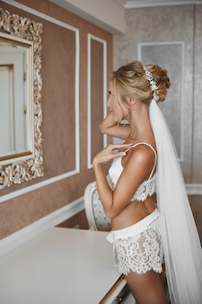 Junge frau mit schlankem körper und platinblondem haar, das nahe dem spiegel im weinleseinnenraum aufwirft. blondes modellmädchen mit schlankem körper und brautfrisur in spitzenwäsche, die im innenraum aufwirft.