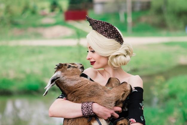 Junge frau mit schönem gesicht und blondem lockigem haar in einem volkskleid, das niedliches weißes kleines lamm hält