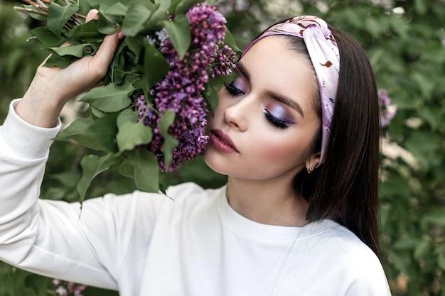 Junge frau mit schönem make-up mit vintage-bandana in weißem, stilvollem hemd mit fliederstrauß, der auf grünem hintergrundlaub im park posiert. attraktives mädchen des frischen porträts mit purpurroten blumen.