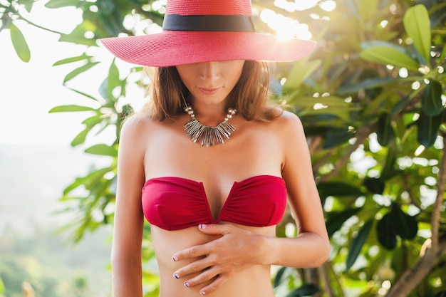 Junge frau mit schönem schlanken körper, der roten bikini-badeanzug, strohhut und halskette trägt, die auf tropischem villenresort im urlaub auf bali entspannen, dünne figur, sommerart-trendzubehör, sonnig